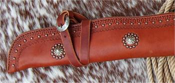 U.S. Marshall rifle scabbard close up with border tooling , spots, conchos and decorative buckles.