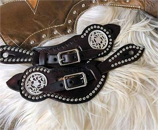 Westrn leather spur straps with border tooling, spots and large decorative concho.