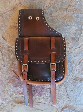 Custom leather saddlebags with two straps, border tooling, spots and grommets for carrying additional equipment.
