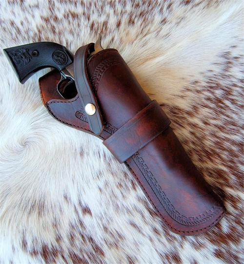 The Woodsman is a classic western leather holster with border tooling and snap down strap to hold gun in the holster.