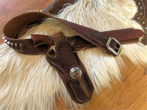 El Dorado leather gunbelt is border tooled, fully stamped holster with concho and bleed knots.