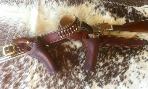 Two holsters with gunbelt, fancy border tooling and choice of buckle color