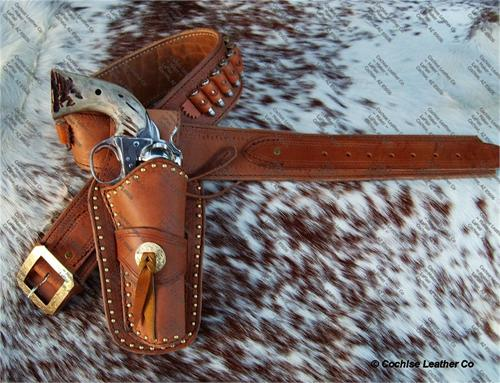Gunbelt with holster, border tooled, floral concho and spots.