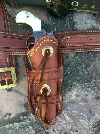 Sundance holster with tooling, spots, concho and bleed knots with gunbelt.