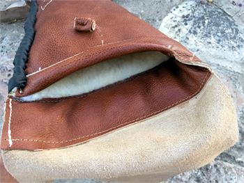 Butt end of vintage sheepskin rifle sleeve with end flap, hand laced bottom and leather closure button